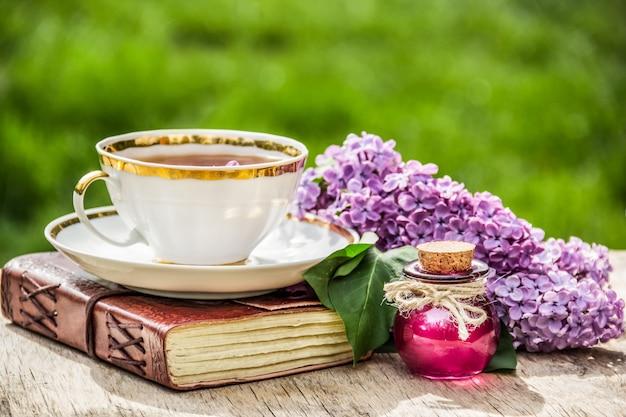 香り高いお茶と新鮮なライラックのカップのクローズアップ