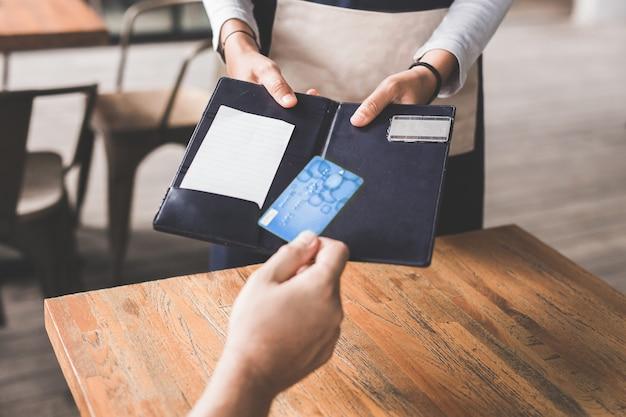 クレジットカードを使用して彼の手形を支払う顧客の手のクローズアップ