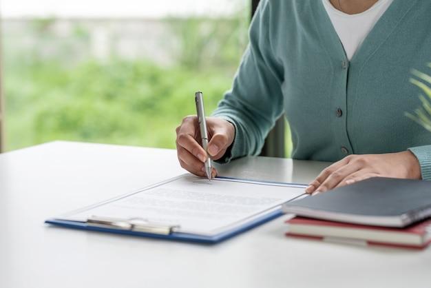 顧客のクローズアップは、オフィスでエージェントと一緒に家を売る契約に署名します。
