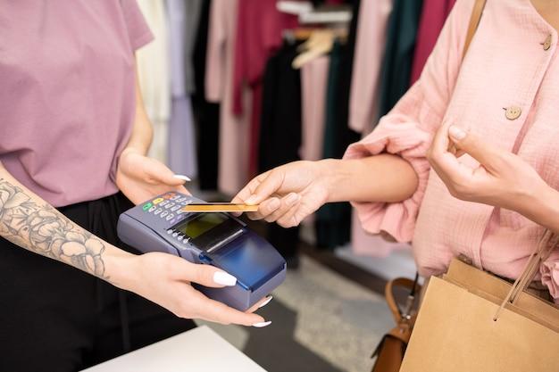 상점에서 신용 카드로 구매 비용을 지불하는 쇼핑백을 든 고객의 클로즈업
