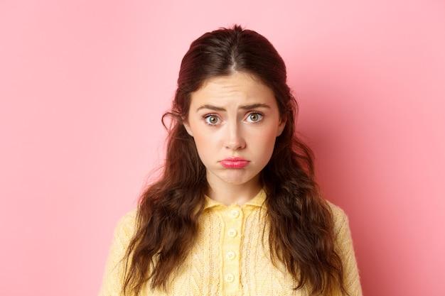 뭔가를 요구하기 위해 슬픈 삐죽 얼굴을 만드는 귀엽고 수줍은 소녀의 닫습니다, 우울한 분홍색 벽에 서서 동정을 원합니다.