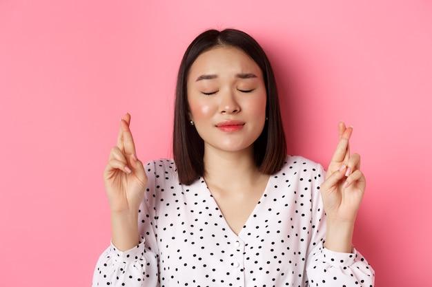 소원을 만드는 귀여운 아시아 소녀의 근접 촬영, 눈을 감고 손가락 희망,기도하고 분홍색 위에 서