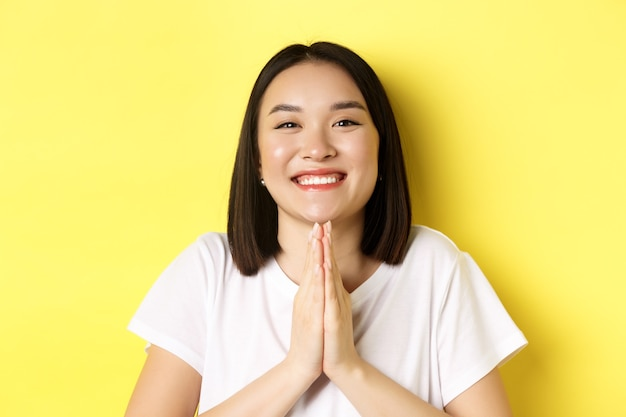 ありがとうと言って笑顔、ナマステで手をつないで、ジェスチャーを祈って、黄色の背景の上に立っているかわいいアジアの女性のクローズアップ。