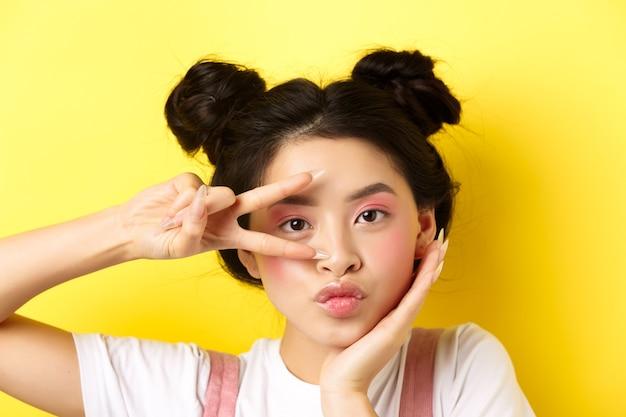 밝은 매력적인 메이크업, 긴 손톱, v 기호를 표시하고 카메라에 바보 같은 삐죽, 노란색에 귀엽다 서있는 귀여운 아시아 여자의 근접.