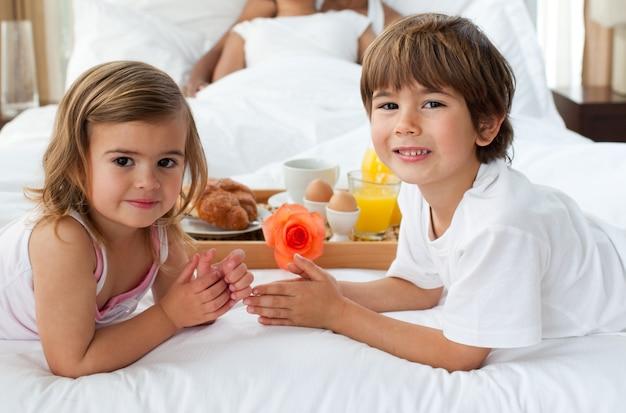 かわいい兄と妹の朝食を親と一緒にしているクローズアップ