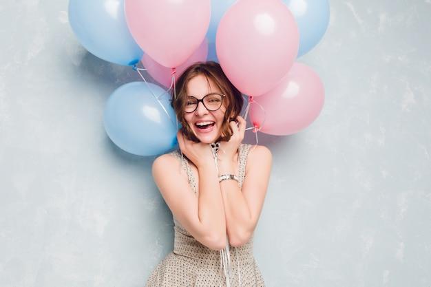 스튜디오에 서, 널리 웃 고 파란색과 분홍색 풍선을 가지고 노는 귀여운 갈색 머리 여자의 클로즈업. 그녀는 재미
