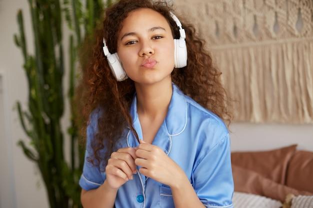 ヘッドフォンでお気に入りのロマンチックな音楽を聴いて、キスを送信し、幸せそうに見えるかわいい巻き毛のアフリカ系アメリカ人の若い女性のクローズアップ。