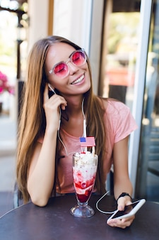 상단에 체리와 아이스크림을 먹고 카페에 앉아 귀여운 여자의 클로즈업. 그녀는 분홍색 상단과 분홍색 안경을 착용합니다. 그녀는 스마트 폰으로 음악을 듣고 미소를 지었다. 그녀는 길고 검은 머리카락을 가지고 있습니다.