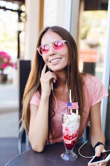 Крупный план милой девушки, сидящей в кафе, едят мороженое с вишней на вершине. она носит розовый топ и розовые очки. она слушает музыку на смартфоне и улыбается. у нее длинные темные волосы