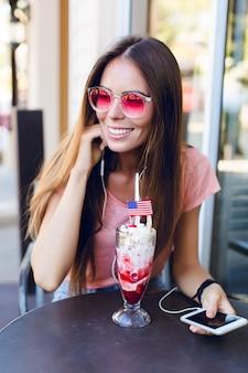 桜を上にアイスクリームを食べるカフェに座っているかわいい女の子のクローズアップ。彼女はピンクのトップとピンクの眼鏡をかけています。彼女はスマートフォンで音楽を聴き、笑顔を見せます。彼女は長い黒髪をしています
