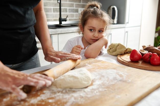 彼女の母親が木製の麺棒で生地を広げているのを見ているかわいい女の子のクローズアップ。ママと娘は一緒にピザを作ります。