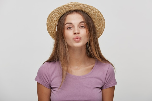 吹くキスを送信するピンクのリボンと麦わら帽子のカジュアルな服装でかわいい素敵な女性のクローズアップ