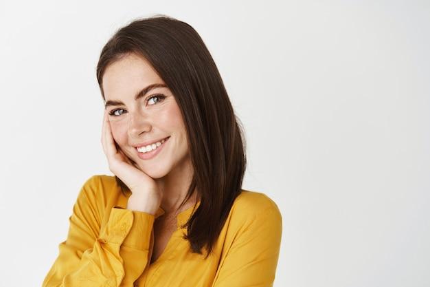 Крупный план милой улыбающейся женщины, кокетливо смотрящей в камеру, трогающей щеку и краснеющей, стоящей на белой стене в желтой рубашке
