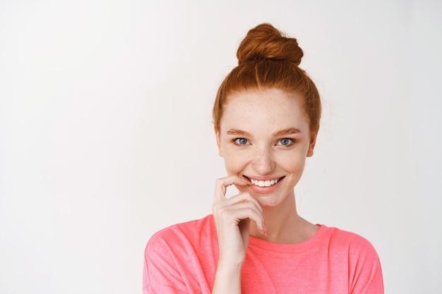 お団子に生姜髪をとかし、白い歯で笑って、輝く肌を見せて、顔に化粧をしていない、白い壁の上に立っているかわいい10代の女性のクローズアップ