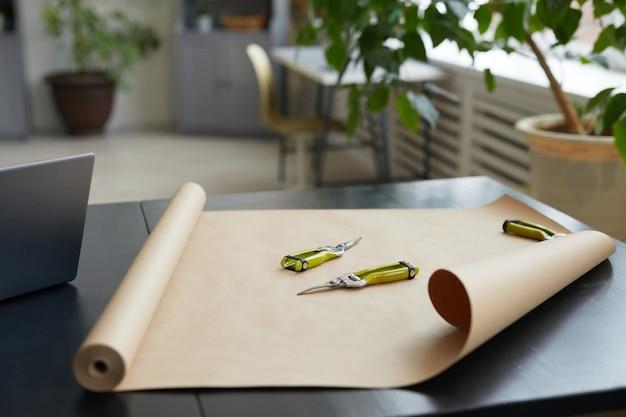 Крупным планом режущие инструменты и крафт-бумага на столе в мастерской флористов, копировальное пространство