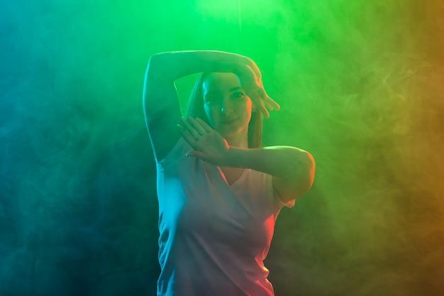 カラフルな背景に踊る若い女性のクローズアップ。