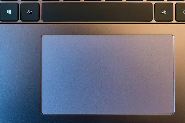 Закройте темно-серый компьютерный тачпад с черной клавиатурой