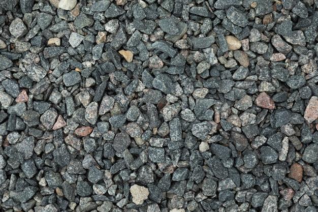 Крупный темно-серый гравий, лежащий на земле