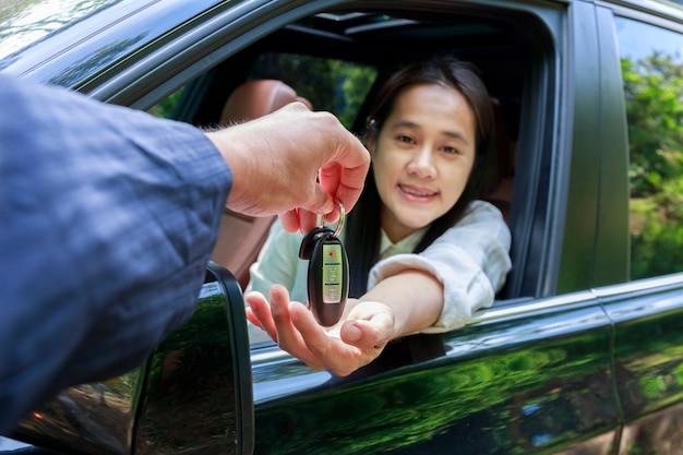 新しい所有者の車に鍵を与えるディーラーのクローズアップ。新車。田舎道での試乗のために女性の自動車の鍵を与える自動車ディーラー。