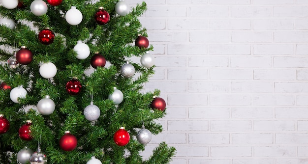 Закройте украшенную елку с красочными шарами над белой кирпичной стеной