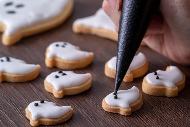 Крупным планом украшения милые пряники с привидениями на хэллоуин с глазурью и кремом.