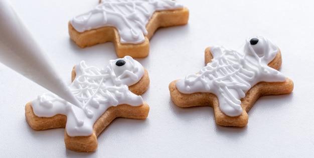 Крупным планом украшения милые пряники на хэллоуин с глазурью с кремом.