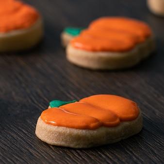 フロスティングアイシングクリームトッピングバッグでかわいいハロウィーンのカボチャジンジャーブレッドクッキーを飾るのクローズアップ。