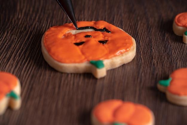 Крупным планом украшения милые тыквенные пряники на хэллоуин с глазурью