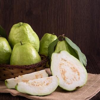 暗い木製のテーブルの背景に分離された新鮮な緑の葉で設定されたおいしい美しいグアバのクローズアップ。