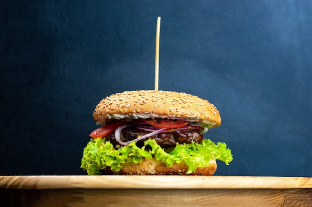 レタスとおいしい新鮮な自家製ハンバーガーのクローズアップ