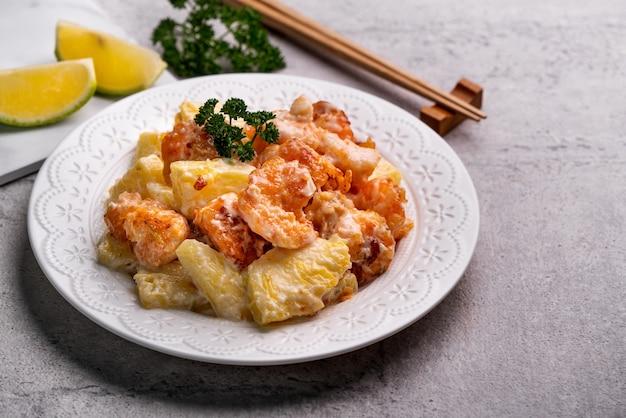 Крупным планом вкусные жареные шарики из креветок с ананасом и майонезным соусом в белой тарелке на сером столе