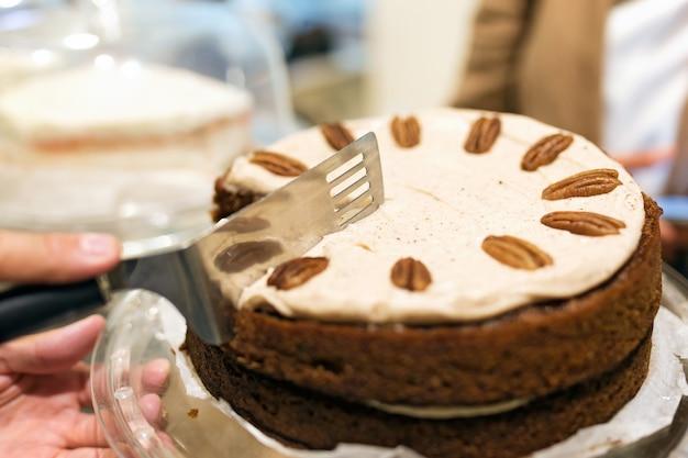 커피숍에서 공유하기 위해 얇게 썬 맛있는 수제 당근 케이크의 클로즈업.