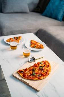 リビングルームの大理石のテーブルでおいしい自家製イタリアンピザのクローズアップ