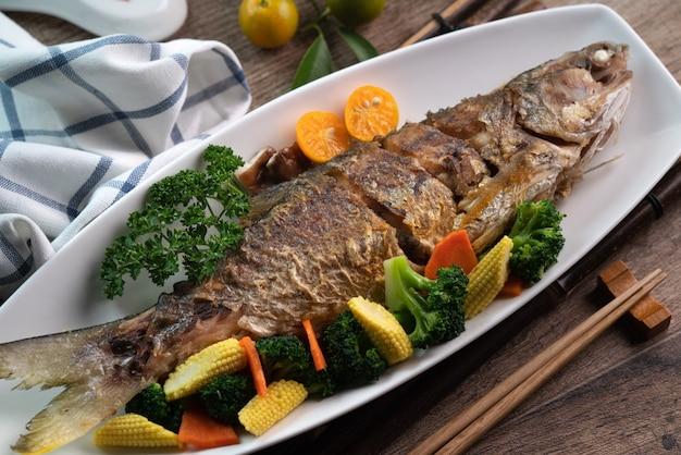 나무 테이블에 야채와 흰 접시에 맛있는 후라이 팬에 튀긴 생선 요리 닫습니다.