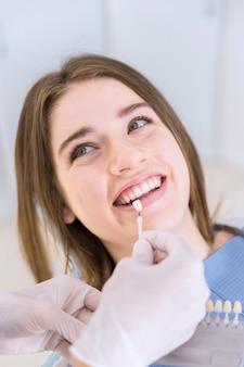 女性の患者の歯のための陰を選ぶ歯の色のサンプルで歯科医のクローズアップ