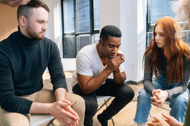 그룹 치료 세션에 원에 앉아 문제를 공유하는 우울한 아프리카계 미국인 젊은 남자의 클로즈업. 전문 심리학자와 정신 건강 문제에 대한 그룹 컨설팅의 개념.