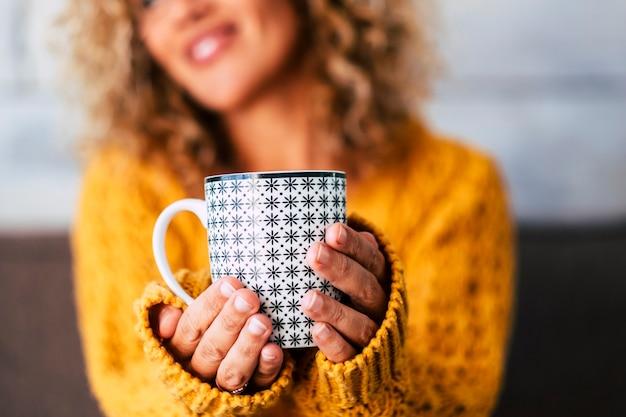 お茶、コーヒー、または大人の白人女性の手で保持された重い飲み物を入れたデザインのトレンディなマグの接写