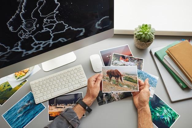 Крупный план дизайнера, смотрящего на фотографии, сидя на своем рабочем месте перед монитором компьютера в офисе