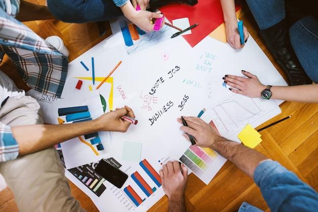彼らの仕事のためのいくつかの新しいアイデアに取り組んでいるデザイナーの手のクローズアップ。