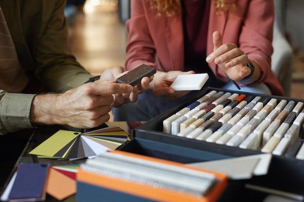 테이블에 앉아 팀에서 색상을 선택하는 타일 패턴을 검토하는 디자이너의 클로즈업