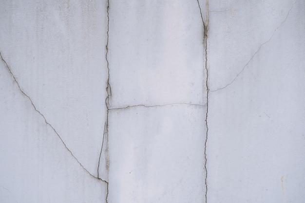 Конец вверх деталей трескает бетонную стену, предпосылку стены цемента