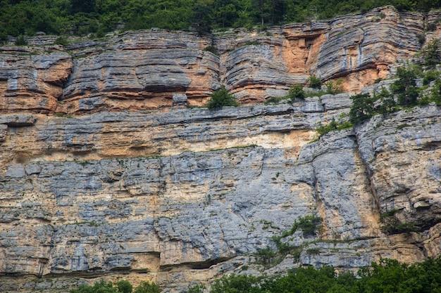 自然公園の山の頂上にある風化した花崗岩の崖の侵食の抽象的な天然石のロックカットテクスチャ断面の詳細のクローズアップ。テキスト用のスペースをコピーします。