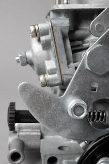 Закройте детали автомобильного карбюратора на сером фоне, небольшая глубина фокуса. автозапчасти.