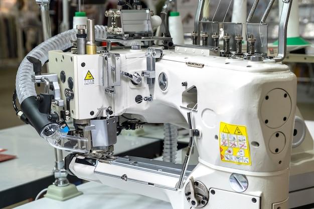 Крупный план деталей современной белой профессиональной электрической швейной машины на столе на фабрике. место работы швеи. нет людей.