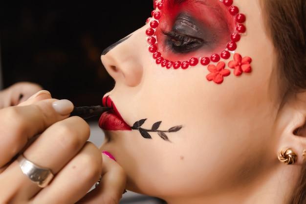Закройте подготовку макияжа dia de los muertos для красивой девушки.