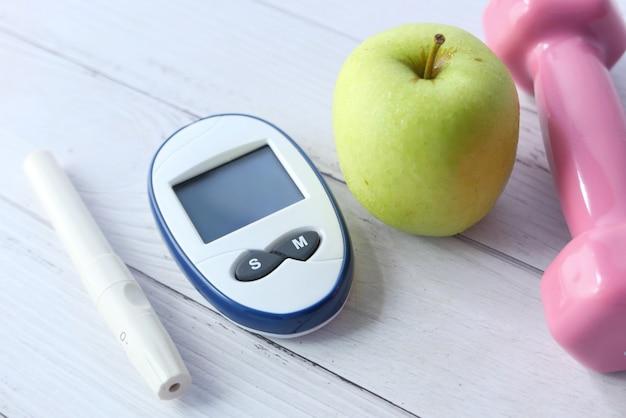 Закройте инструменты измерения диабета, яблоко и гантель на столе.