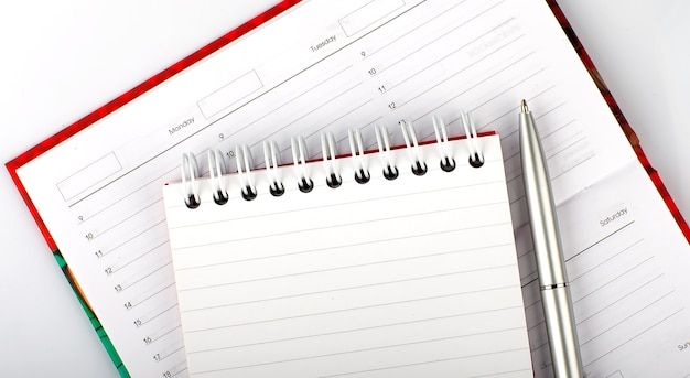 Крупный план дневника, блокнота и ручки на деревянном