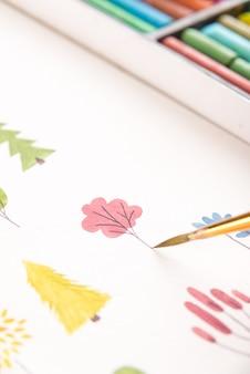 ブラシと水彩絵の具で紙に描かれた色とりどりの花の自然デザインのクローズアップ
