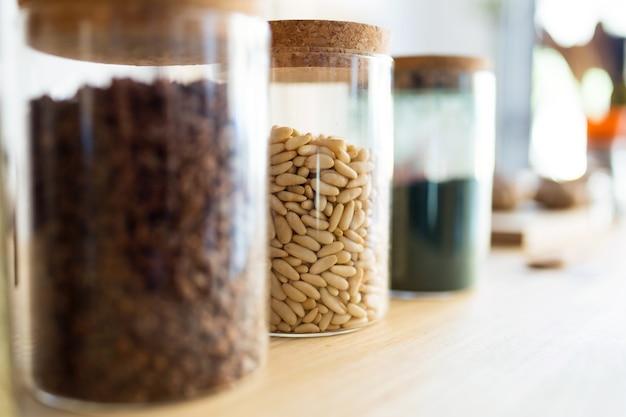 Крупный план различных типов ингредиентов для здорового приготовления пищи в стеклянных банках в магазине органических продуктов.