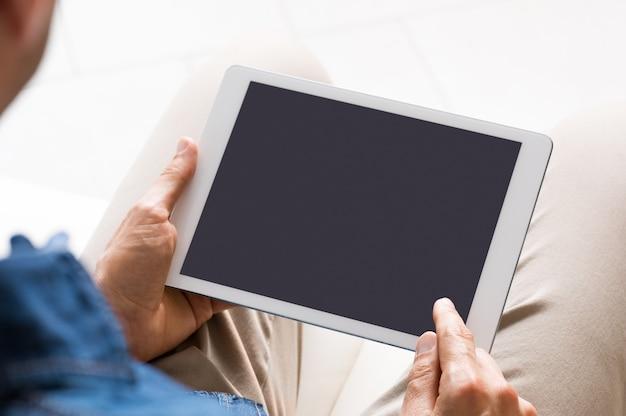 男がそれに取り組んでいる間、デジタルタブレット画面のクローズアップ